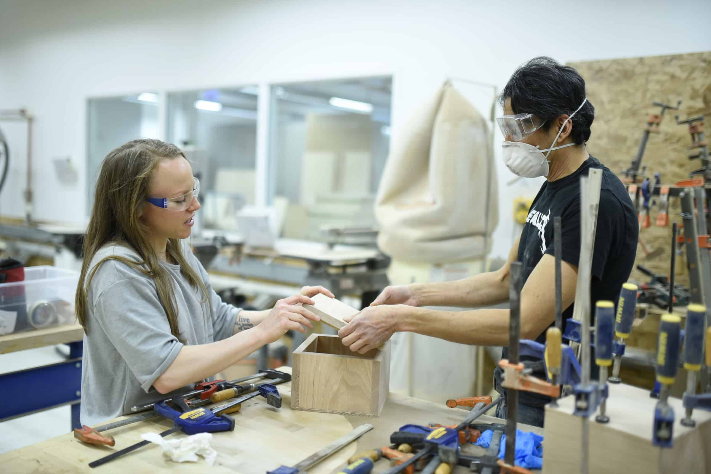 a woman and man work in the woodshop at mHUB